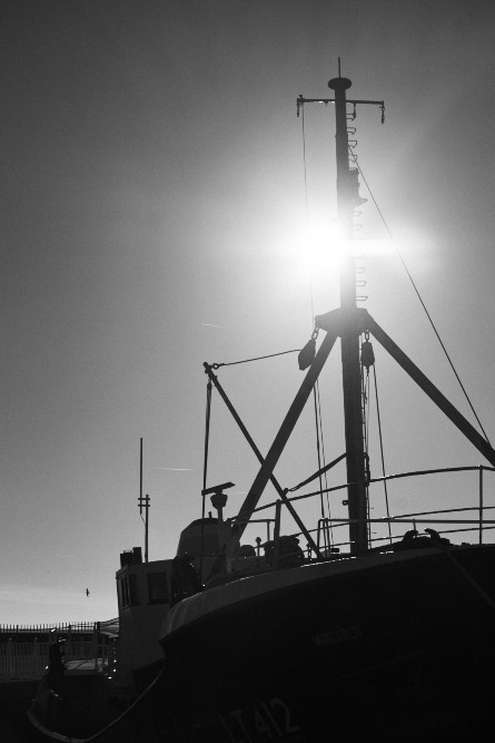 sun behind a boat's mast