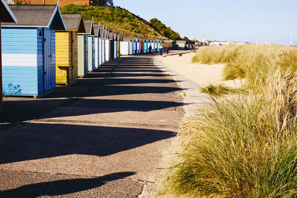 row of beach huts in afternoon sun