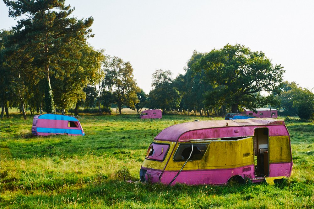 colourful abandoned caravans in a field