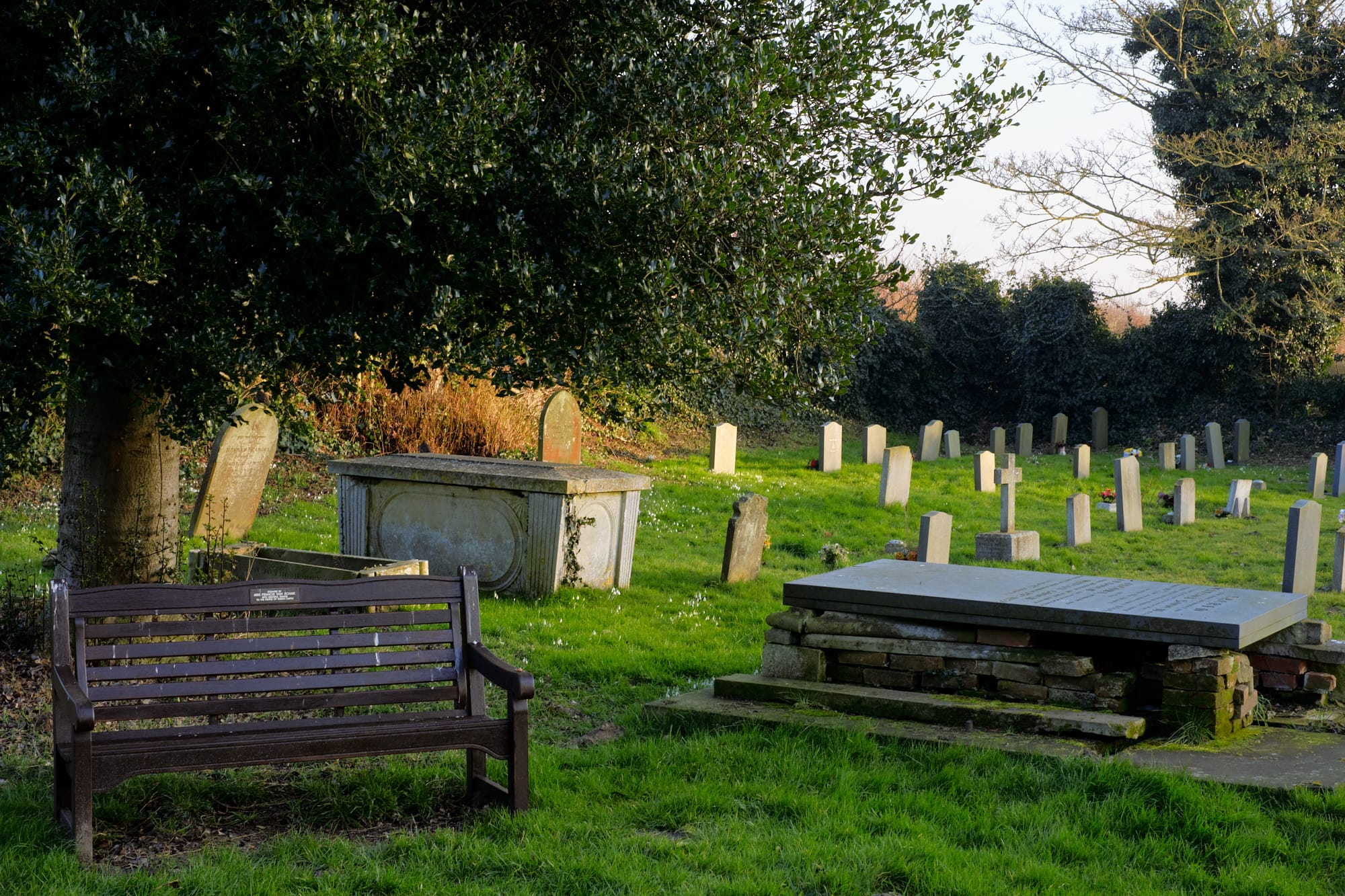 bench and gravestones in church grounds