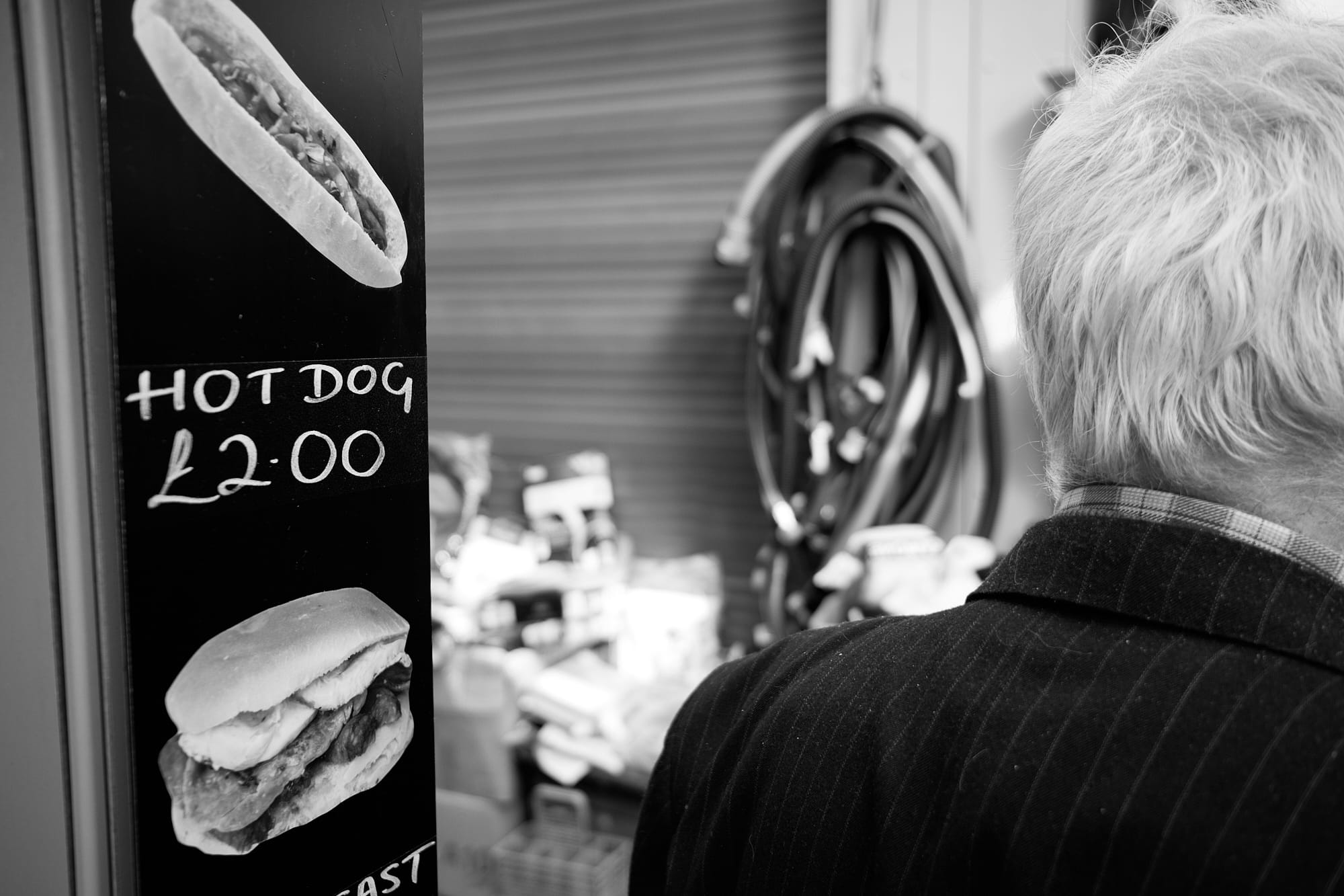 'Hot Dog' sign and back of old man's head