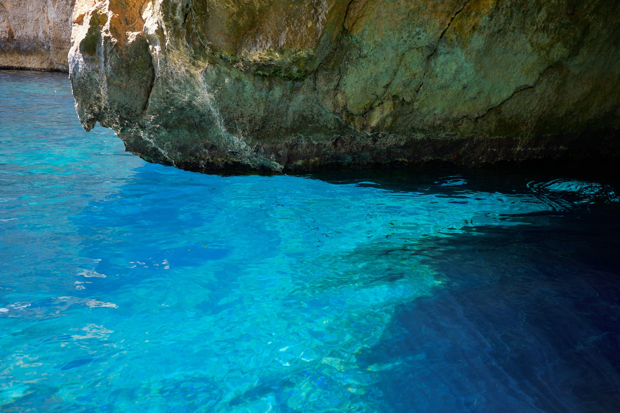 rock overhanging blue water
