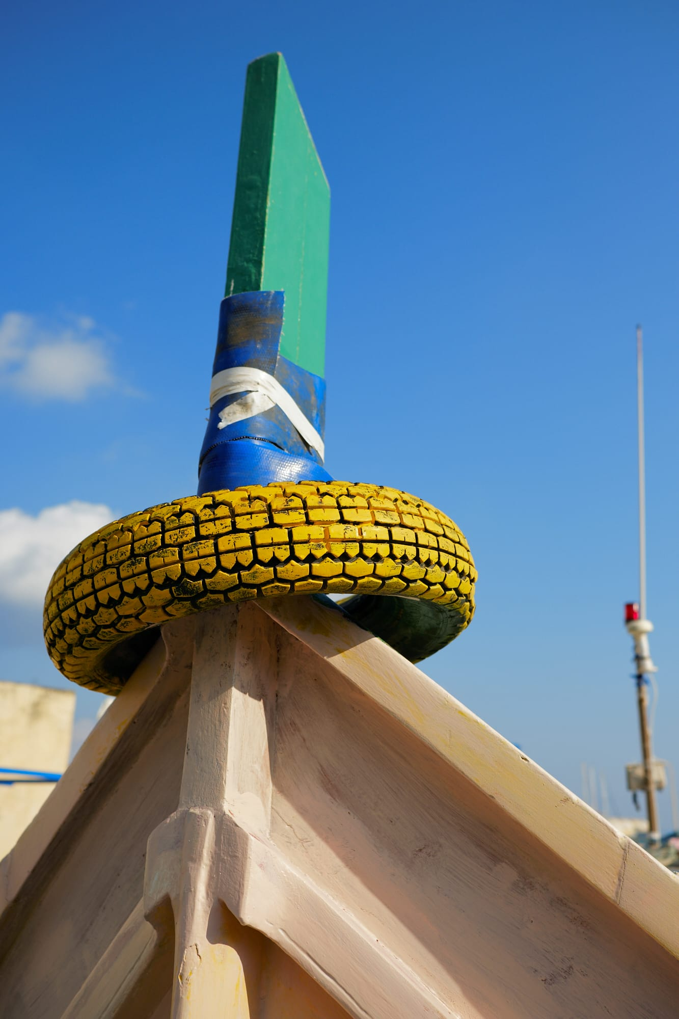 yellow painted tyre on boat prow