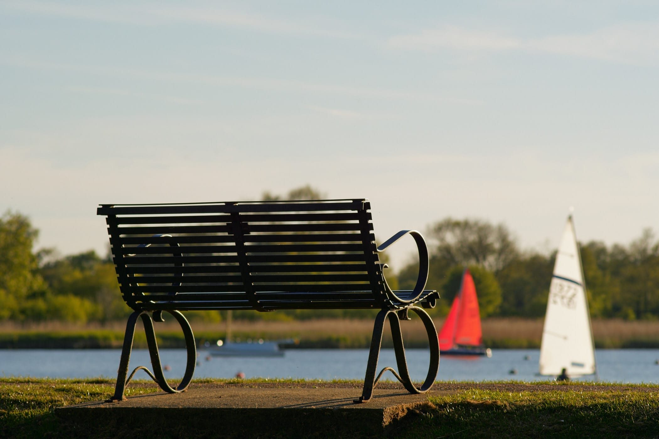 park bench with sailing dinghies in the background
