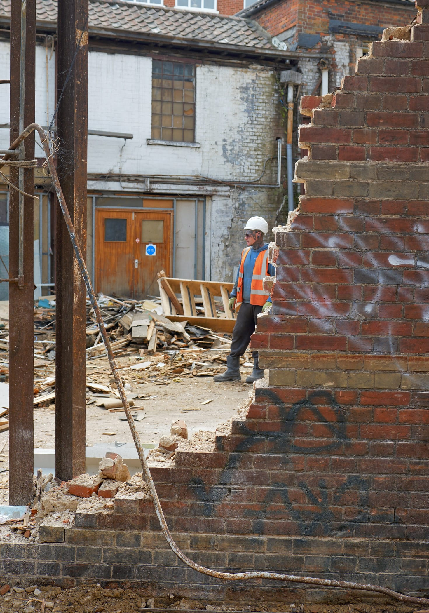 workman behind partially demolished wall